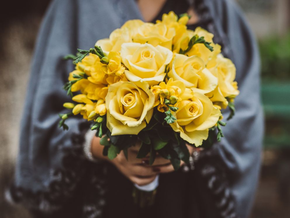PHOTO: A woman holds a bouquet of yellow roses in this stock image.