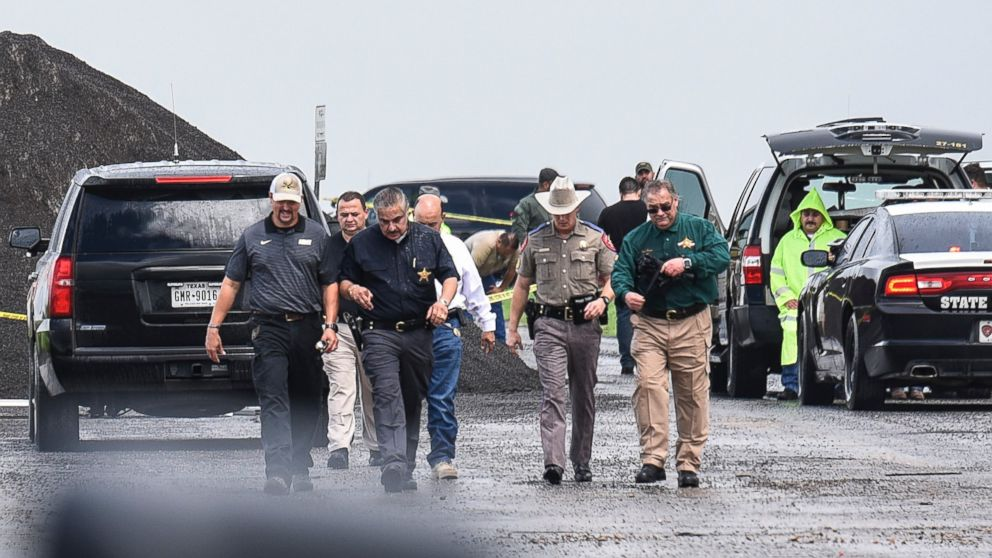 Law enforcement officers gather near the scene where the body of a woman was found near Interstate 35 north of Laredo, Texas on Saturday, Sept. 15, 2018.