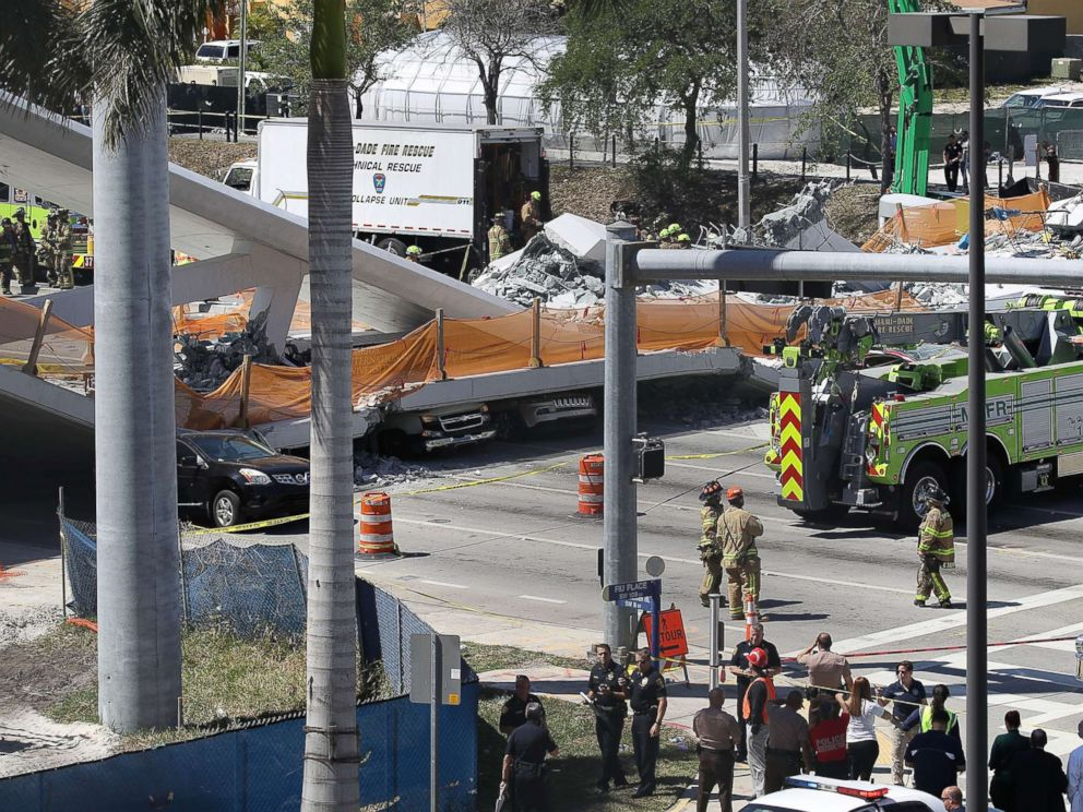 PHOTO: Vehicles are seen trapped under the collapsed pedestrian bridge that was newly built over southwest 8th street allowing people to bypass the busy street to reach Florida International University, March 15, 2018 in Miami.