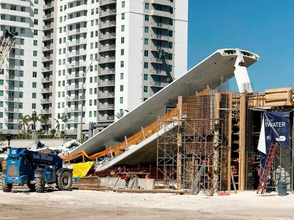 PHOTO: A crane is seen near a newly installed pedestrian bridge, that collapsed, over a six-lane highway in Miami, March 15, 2018.