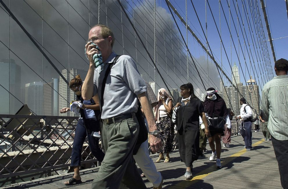 PHOTO: People walk over New Yorks Brooklyn Bridge from Manhattan to Brooklyn following the collapse of both World Trade Center towers on Sept. 11, 2001.