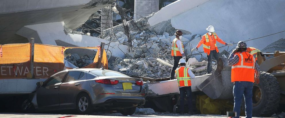 PHOTO: Workers, law enforcement and members of the National Transportation Safety Board investigate the scene, March 16, 2018, where a pedestrian bridge collapsed on March 15 a few days after it was built, in Miami.