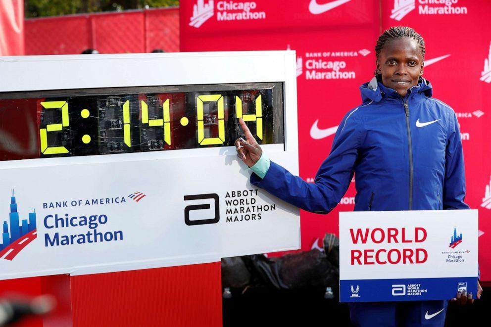 PHOTO: Kenyas Brigid Kosgei celebrates winning the womens marathon next to her new world record at the Chicago Marathon, Oct. 13, 2019.