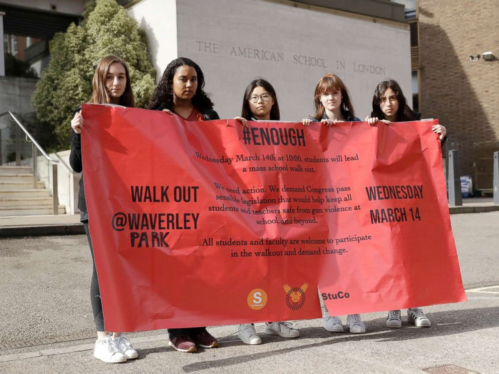PHOTO: Students pose for photographs with a banner outside the front of the American School in London, after taking part in a 17-minute walkout in the school playground, which was attended by approximately 300 students aged 14-18, March 14, 2018.