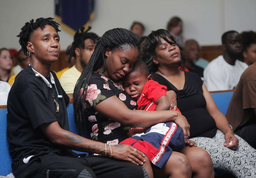 Britany Jacobs, 25, consoles her 5-year-old son Markeis McGlockton Jr., during a vigil for his slain father Markeis McGlockton Sr., 28, while their cousin Mesha Gilbert, 26, left, looks on at Mt. Carmel Baptist Church in Clearwater, Fla., July 22, 2018.
