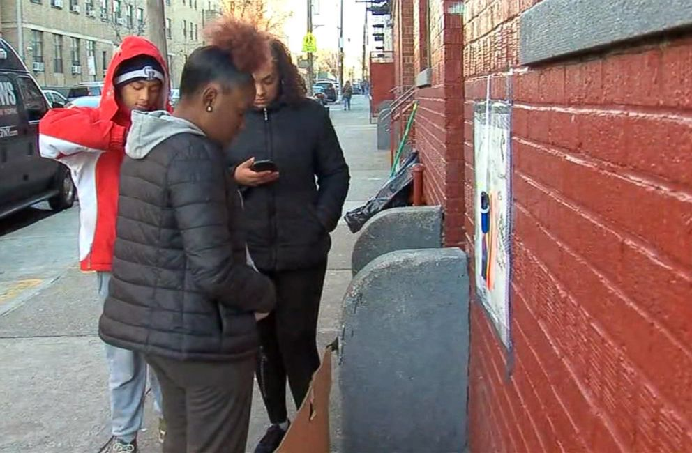 PHOTO: Friends of 17-year-old Angel Reyes-Godoy gather around the stoop where he would often hang out on Bainbridge Avenue in the Bronx borough of New York, Dec. 11, 2018.