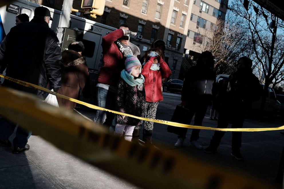 PHOTO: People look at the apartment building where a deadly fire took the lives of 12 people in the Bronx borough of New York, Dec. 29, 2017.