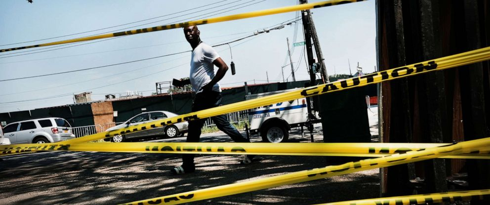 PHOTO: A man walks by police tape in the Brownsville neighborhood in Brooklyn where one person was shot and killed and 11 others were injured after two or more shooters opened fire during a massive block party on July 29, 2019 in New York City.