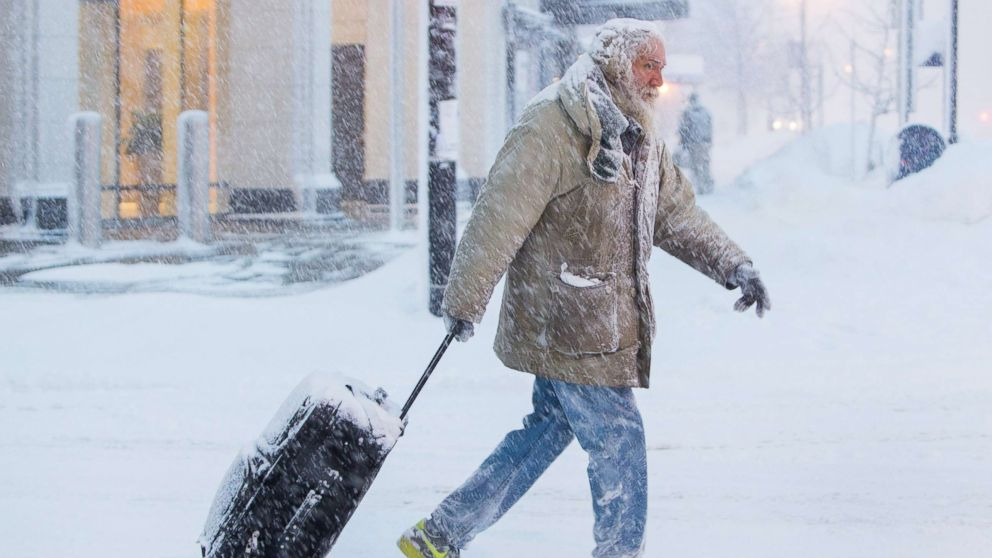Man moves luggage in snow during a winter storm in Buffalo, N.Y., Jan. 30, 2019.