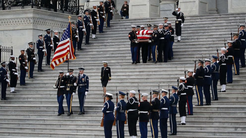 The flag-draped casket of former President George H.W. Bush is carried by a joint services military honor guard from the U.S. Capitol, Dec. 5, 2018, in Washington.