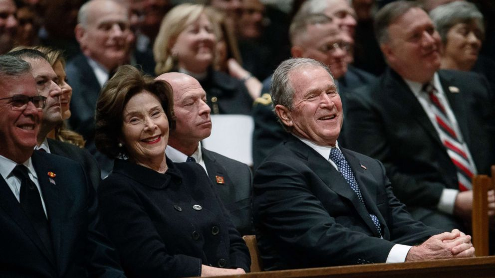 Jeb Bush, Laura Bush, and former President George W. Bush share a laugh as a story is told about former President George H.W. Bush during a State funeral at the National Cathedral, Dec. 5, 2018, in Washington.