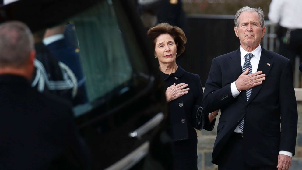Former President George W. Bush and former first lady Laura Bush watch as the flag-draped casket of former President George H.W. Bush is carried to a State Funeral at the National Cathedral, Dec. 5, 2018 in Washington.