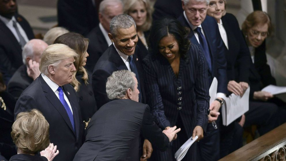 Former president George W. Bush reaches past President Donald Trump to greet former first Lady Michelle Obama during the funeral service former president George H.W. Bush at the Washington National Cathedral, Dec. 5, 2018, in Washington, D.C. Dec. 5, 2018.