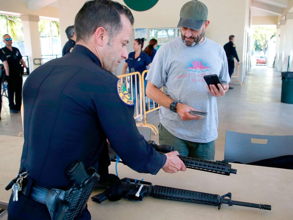 PHOTO: City of Miami Police commander Freddie Cruz (L) accepts two AR-15 rifles from Steven Hemmert (R) during a City of Miami gun buy-back event in Miami, March 17, 2018.