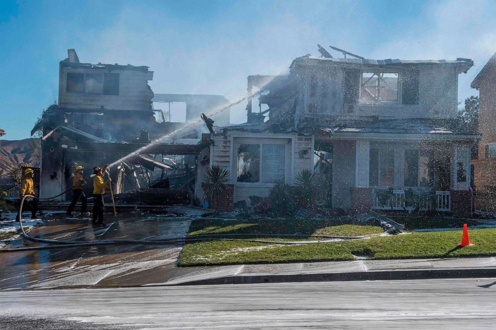 PHOTO: Firefighters hose down a burning house during the Tick Fire in Agua Dulce near Santa Clarita, California on October 25, 2019.