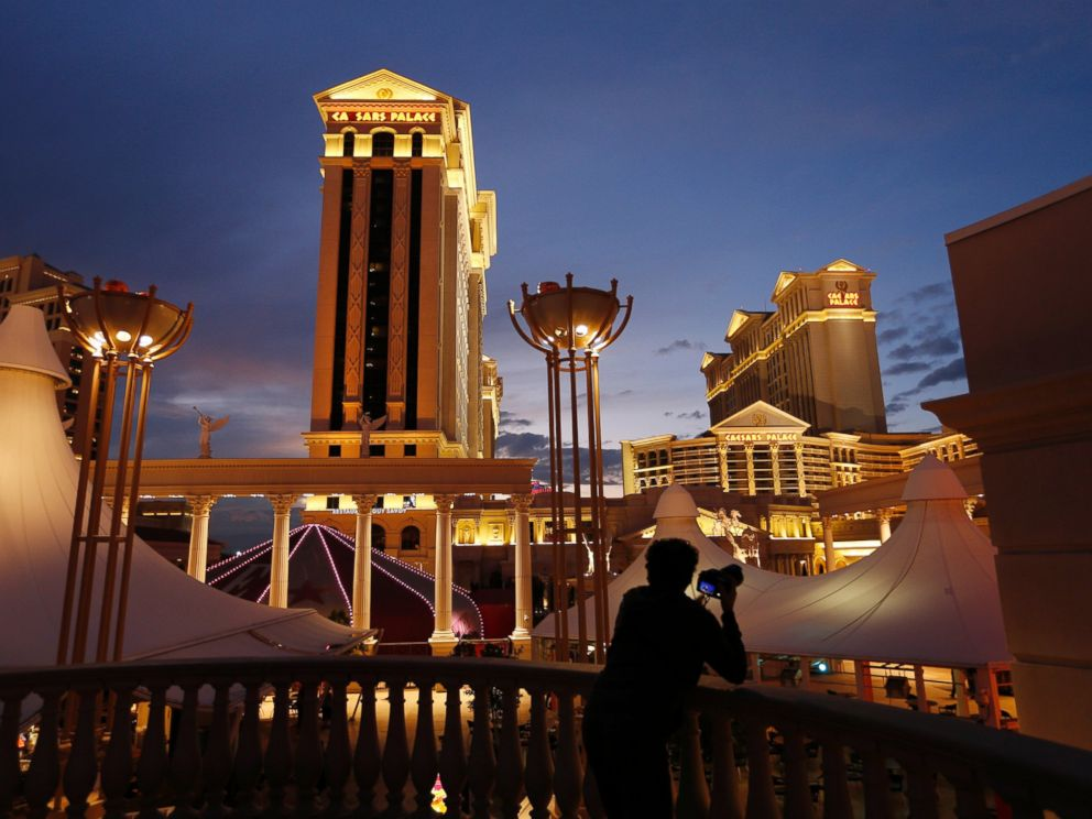 In this Jan. 12, 2015 file photo, a man takes pictures of Caesars Palace hotel and casino, in Las Vegas.  2 people injured by flaming drink at Gordon Ramsay's Las Vegas restaurant caesars palace ap mo 20180804 hpMain 4x3 992