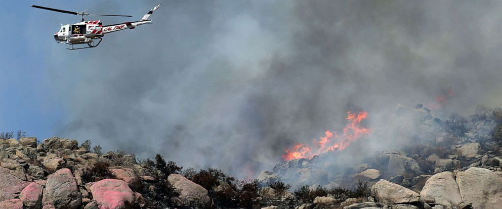 PHOTO: California Fire helicopter makes a pass over the Horseshoe fire as brush crews mop up hot spots above Aswut Circle near Awaal Street in San Jacinto, Calif., Sep 15, 2019.