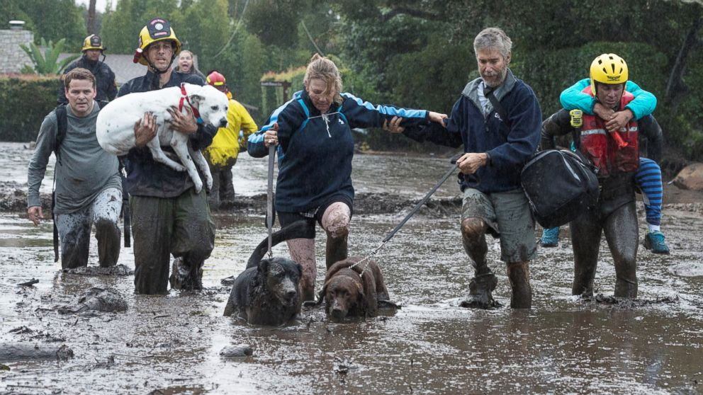 Emergency personnel evacuate local residents and their dogs after a mudslide in Montecito, Calif., Jan. 9, 2018.