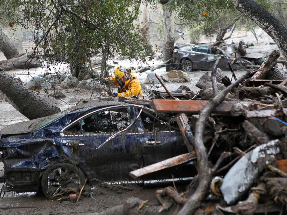 PHOTO: A member of the Long Beach Search and Rescue team looks for survivors in a car in Montecito, Calif., Jan. 9, 2018.