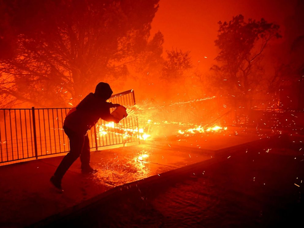 PHOTO: Ozzy Butler pours water on to his deck at his parents house as the Saddleridge Fire burns along Thunderbird Ave. in Porter Ranch, Calif., Oct. 11, 2019.