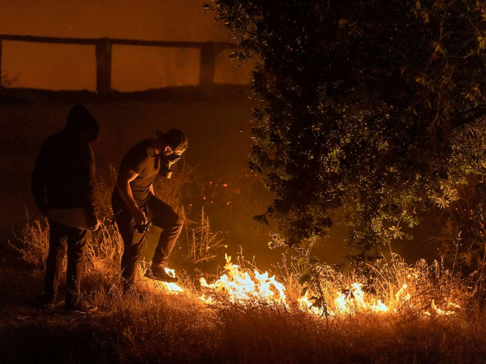 PHOTO: A man stomps on flames of the Saddleridge Fire in the Porter Ranch section of Los Angeles, in the early morning hours of Oct. 11, 2019.