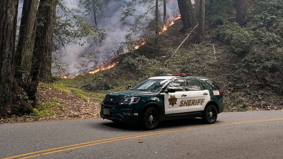PHOTO: A police vehicle is seen under a forest being burned by the CZU August Lightning Complex Fire, Aug. 24, 2020, in Bonny Doon, Calif.