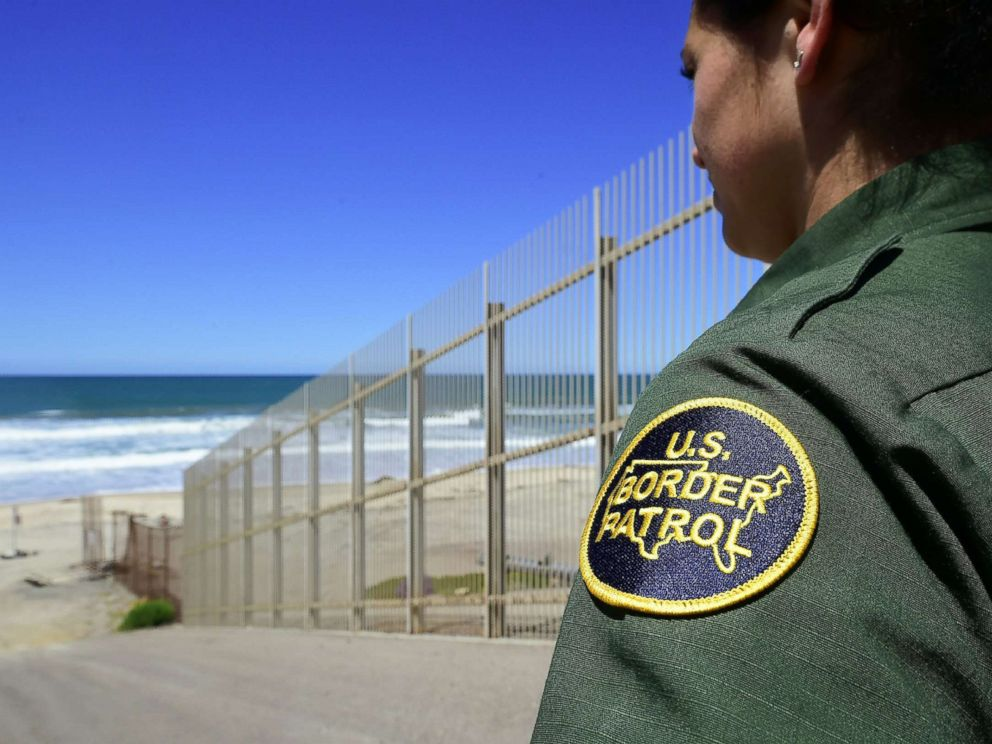 PHOTO: A US Customs and Border Protection agent looks from within the Border Infrastructure System, a no mans land which runs for 14 miles separating California from Mexico on April 17, 2018 in San Diego.