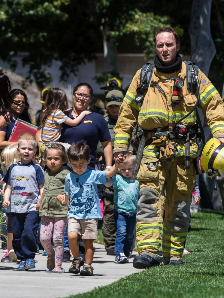 PHOTO: Firefighters and sheriffs deputies escort children from Academy on the Hill pre-k school in Aliso Viejo, Calif., May 15, 2018, after a fatal explosion nearby.