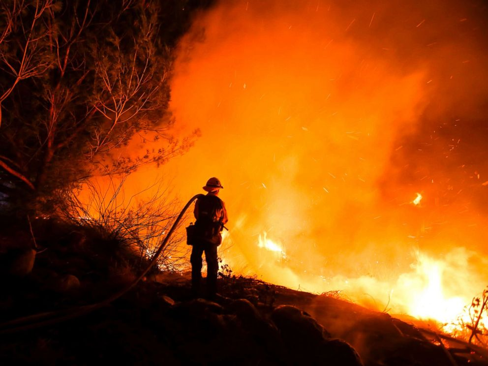 PHOTO: Firefighters battle a wildfire as it burns along a hillside near homes in Santa Paula, Calif., Dec. 5, 2017.
