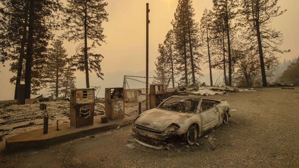 As the Camp Fire burns nearby, a scorched car rests by gas pumps near Pulga, Calif., Nov. 11, 2018.