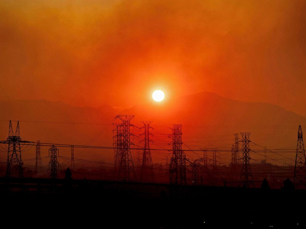 PHOTO: In this Oct. 11, 2019, file photo, smoke from the Saddle Ridge Fire hangs above power lines as the sun rises in Newhall, Calif.