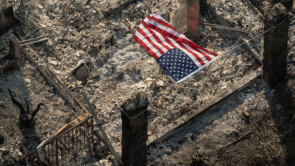 An American flag flies over the remains of a Coffey Park home following the Tubbs fire in Santa Rosa, Calif.