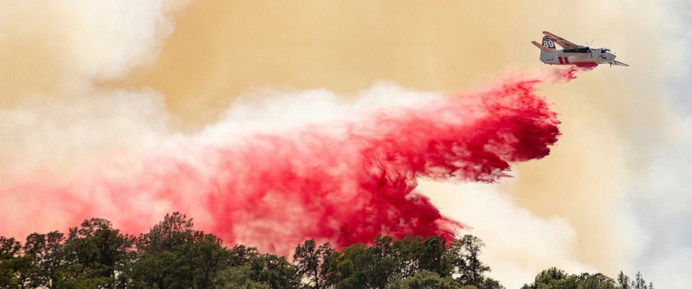 PHOTO: A Cal Fire aircraft drops fire retardant on a hillside in an attempt to box in flames from a wildfire called the Sand Fire in Rumsey, Calif., Sunday, June 9, 2019.