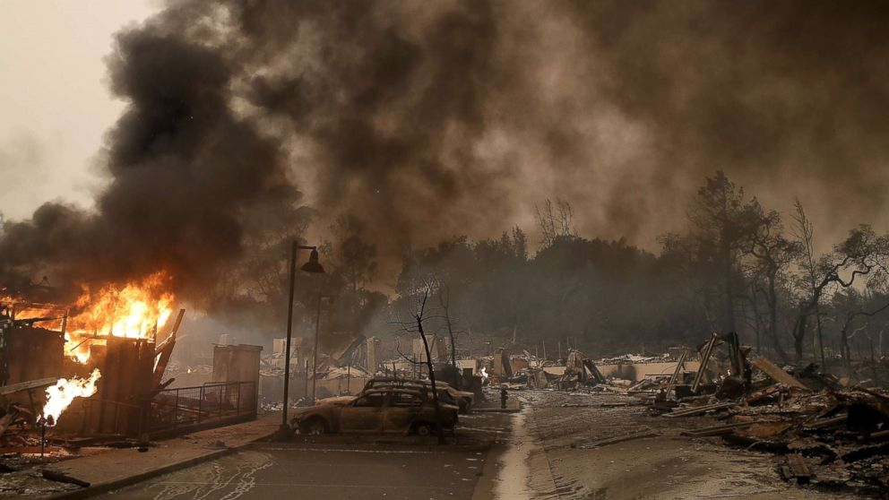 Burned out cars sit next to a building on fire in a fire ravaged neighborhood, Oct. 9, 2017, in Santa Rosa, Calif.