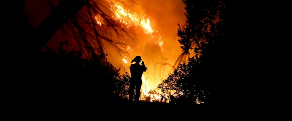 PHOTO: A firefighter takes a cell phone picture during a wildfire, Dec. 16, 2017, in Montecito, Calif.