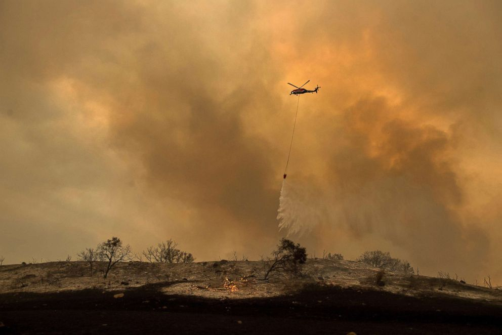 PHOTO: A helicopter drops water while trying to keep a wildfire from jumping Santa Ana Road near Ventura, Calif., Dec. 9, 2017.