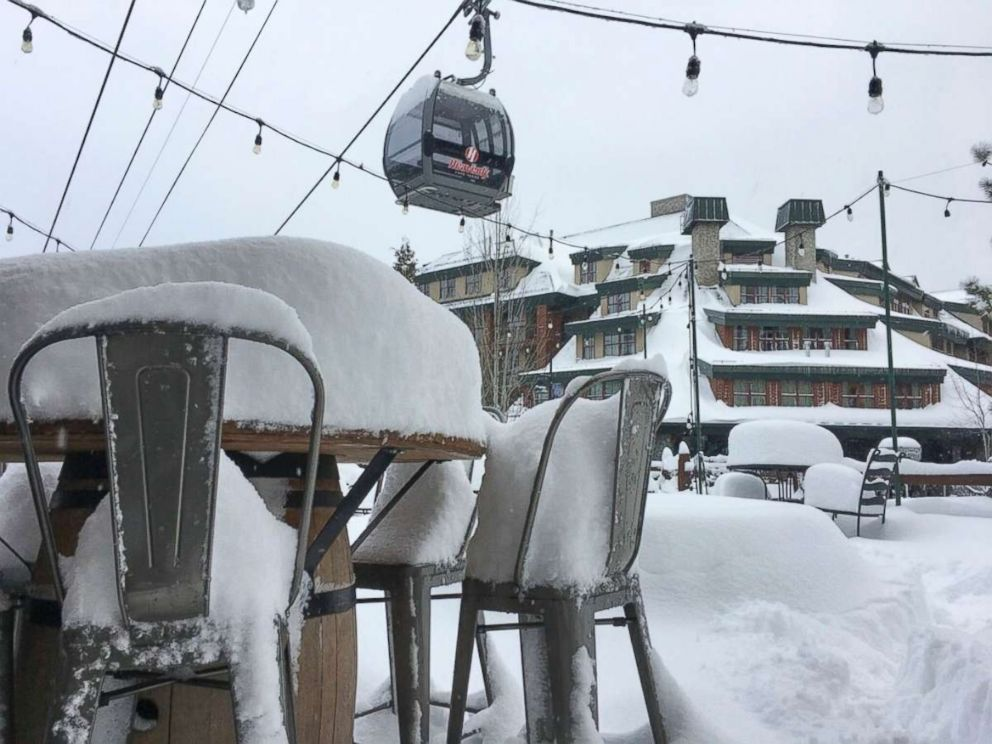 In this photo provided by the Heavenly Mountain Resort, fresh snow covers most of a table and chairs Friday, March 2, 2018, in South Lake Tahoe, Calif. A blizzard warning was in effect for parts of the Sierra Nevada.
