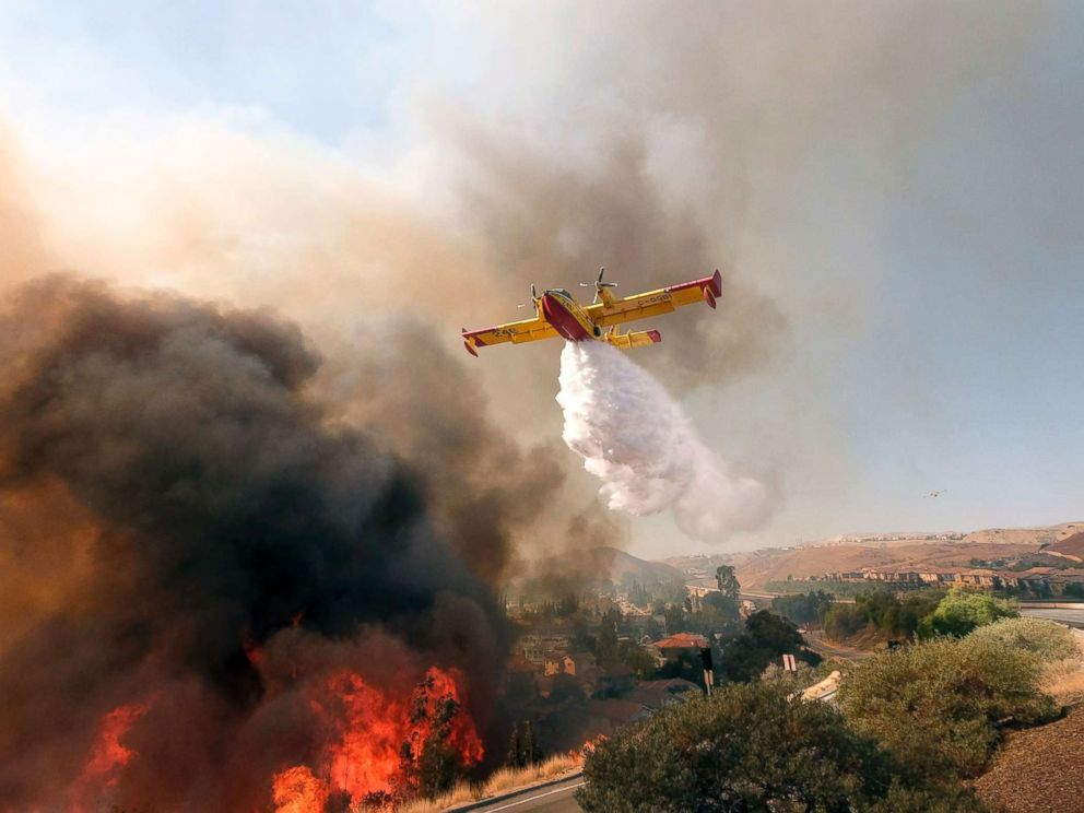 PHOTO: An air tanker drops water on a fire along the Ronald Reagan (118) Freeway in Simi Valley, Calif., Nov. 12, 2018.