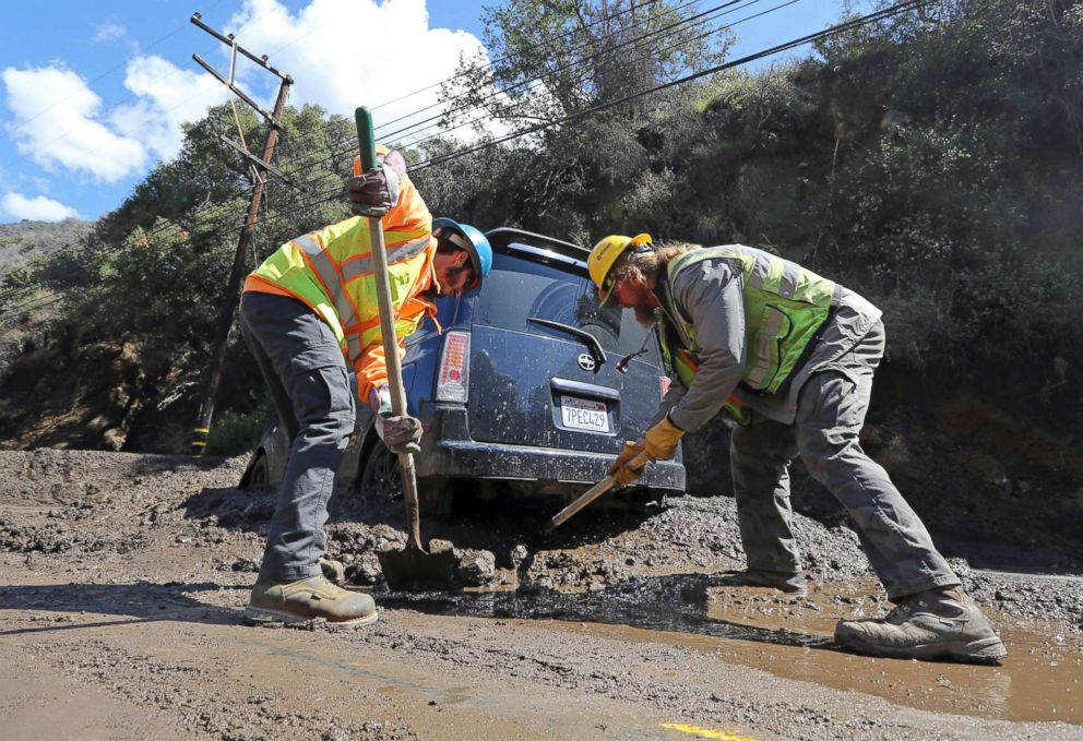 PHOTO: Workers clear mud and debris from under a trapped car after mudslides from heavy rain overnight caused the closure of Topanga Canyon Boulevard, a key mountain highway over the Santa Monica Mountains, above Malibu, Calif., March 15, 2018.