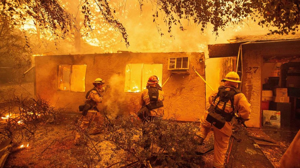 Firefighters push down a wall while battling a fire in an apartment complex in Paradise, Calif., Nov. 09, 2018.