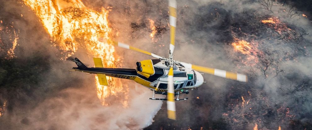 PHOTO: A Los Angeles County Fire helicopter flies over the Skirball Fire which began early morning in Bel-Air, Calif., Dec. 6, 2017.