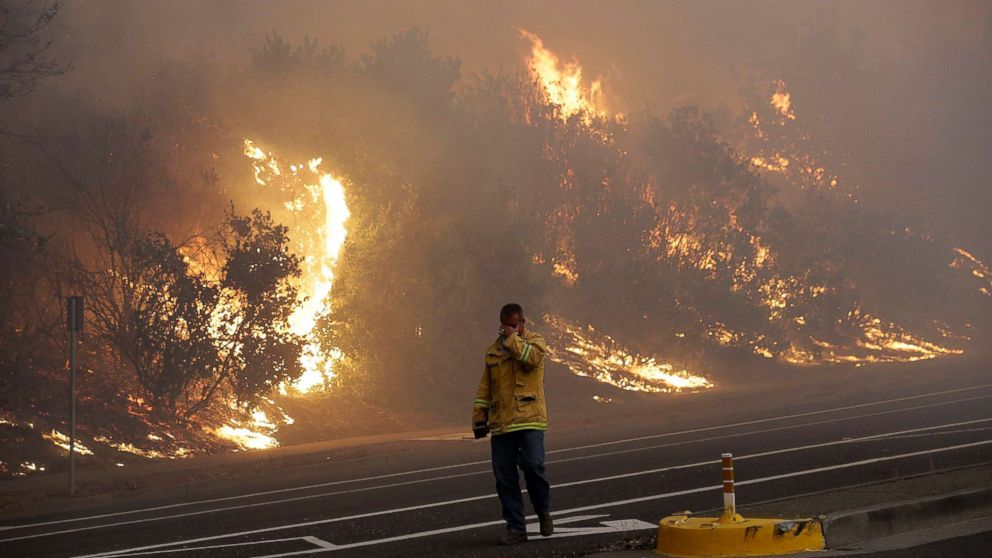 A firefighter covers his eyes as he walks past a burning hillside in Santa Rosa, Calif., Oct. 9, 2017.