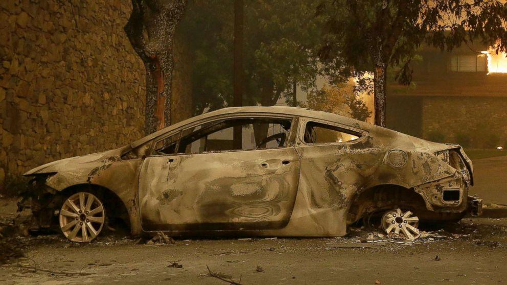 The remains of a car sits near the Fountaingrove Inn Hotel as it burns at rear in Santa Rosa, Calif., Oct. 9, 2017.