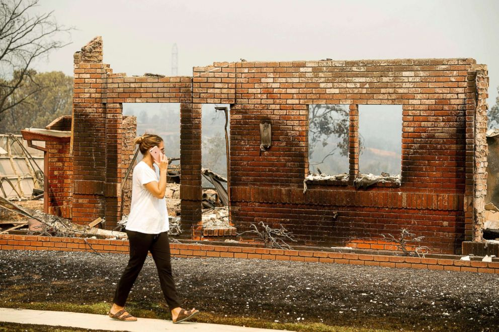 PHOTO: A woman surveys damage to her grandmothers house after the Carr Fire burned through Redding, Calif., July 27, 2018.