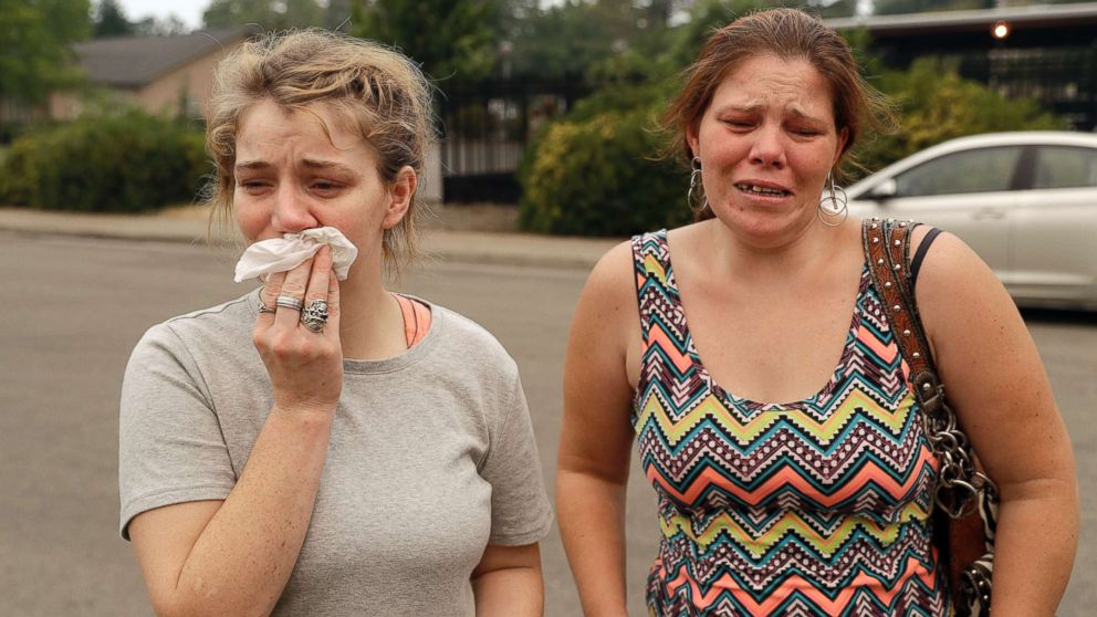 Sherry Bledsoe, left, cries next to her sister, Carla, outside of the sheriff's office after hearing news that Sherry's children, James and Emily, and grandmother, Melody Bledsoe, were killed in a wildfire, July 28, 2018, in Redding, Calif.