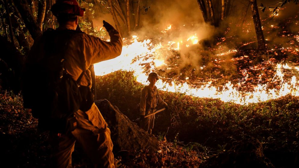 CALFIRE firefighter Tim Zanotelli, center, receives instructions from Captain Gary Mattingly, left, while performing a firing operation to prevent the flames from crossing Highway 29, north of Calistoga, Calif., Oct. 12, 2017.