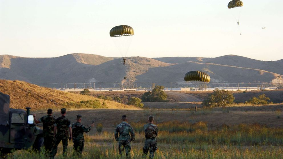 Soldiers parachute from a helicopter during combat readiness training, Sept. 25, 2001 at Camp Pendleton, Calif.