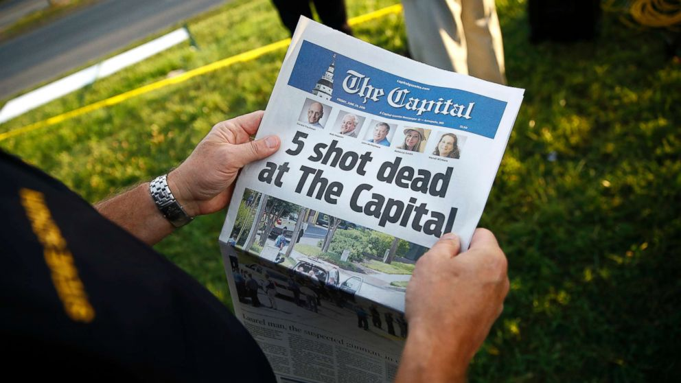 Steve Schuh, county executive of Anne Arundel County, holds a copy of The Capital Gazette near the scene of a shooting at the newspaper's office, June 29, 2018, in Annapolis, Md.
