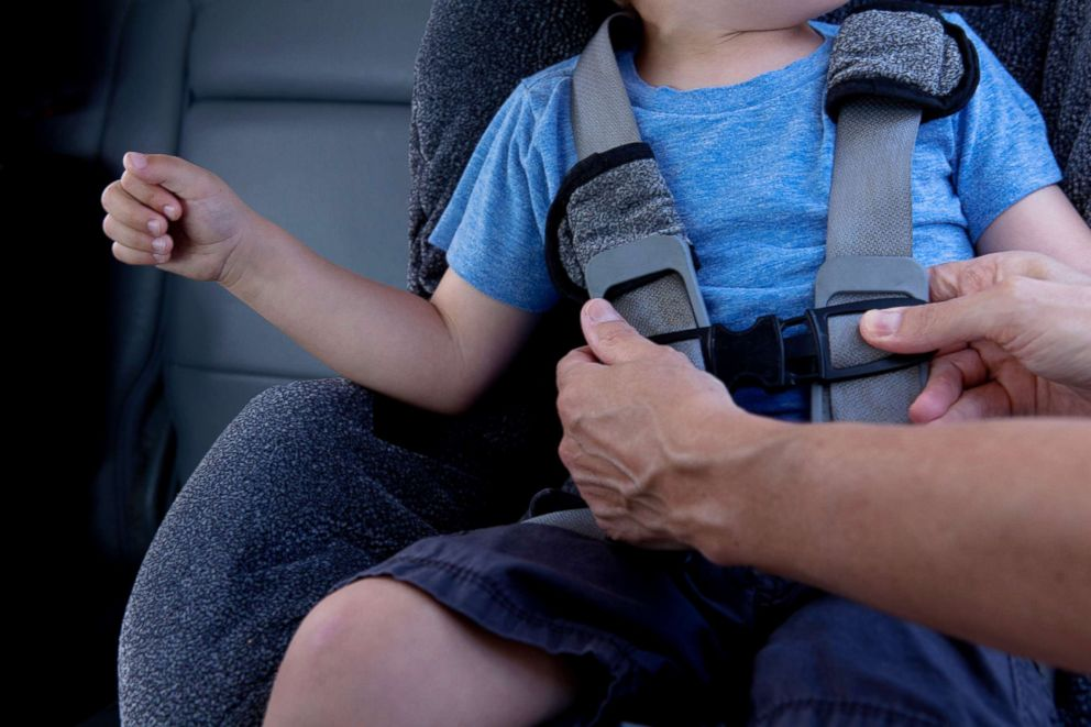 PHOTO: A parent fasten a child on a car seat in this undated stock photo.
