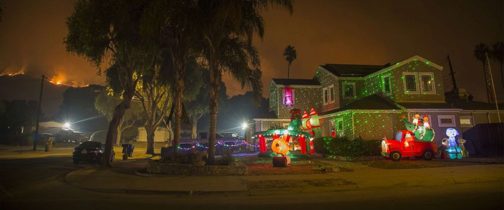PHOTO: Christmas decorations illuminate a house as the growing Thomas Fire advances toward Santa Barbara County seaside communities, Dec. 10, 2017, in Carpinteria, Calif.